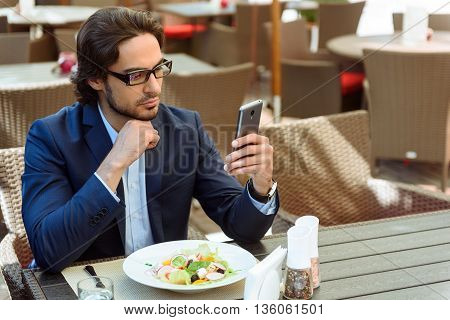 Serious young businessman is having break in cafe. He is using a mobile phone with concentration. Worker is sitting at table near a plate of salad