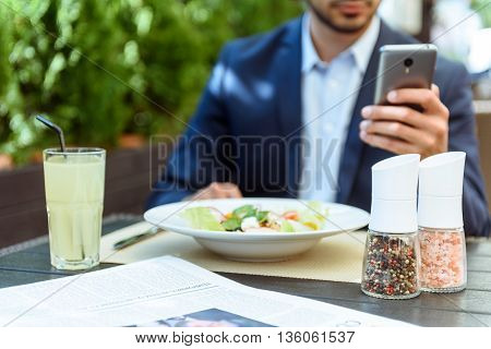 Young man is having lunch in restaurant. He is messaging on a mobile phone. Focus on plate of salad and drink on table