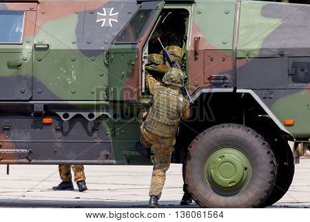 BURG / GERMANY - JUNE 25 2016: german soldier is moving into military infantry vehicle Dingo on open day in barrack burg / germany at june 25 2016