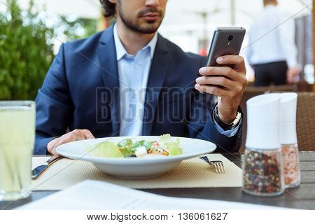 Serious young businessman is eating salad in cafe. He is sitting at table and using a mobile phone