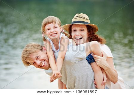 Happy family at water in summer carrying daughter for piggyback ride