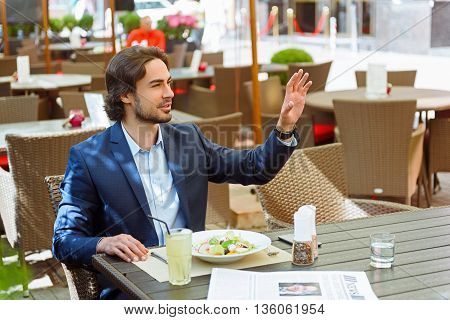 Confident young businessman is calling a waiter. He is sitting at table and raising arm up. Worker is smiling