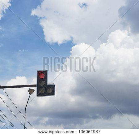 Traffic lights with red light near street lamp and electrical cable; beautiful blue sky and rain cloud background as a copy space.