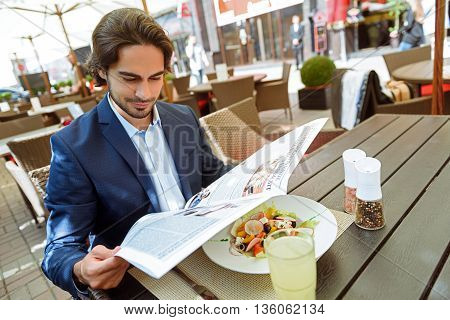 Rich young man is relaxing in cafe outdoors. He is reading a paper with interest. Worker is sitting at table near a plate of healthy salad