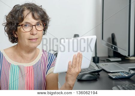 a portrait of a mature woman with a digital tablet