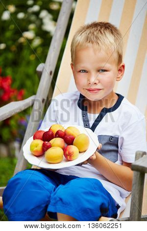 Proud boy sitting in garden with his own fruit harvest
