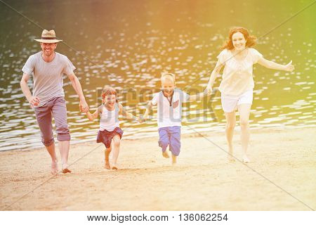 Happy family with two children running in summer on a beach