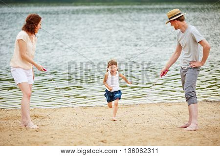 Happy family with smiling daughter jumping rope in summer on a beach