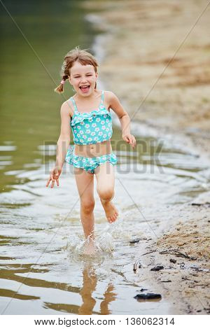 Happy girl running through water on beach of a sea