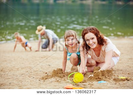 Two parents play with their kids on a beach in summer