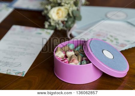 Box of candy on wooden table near flowers