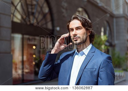 Confident young man is using mobile phone for communication. He is standing near a building and looking forward pensively
