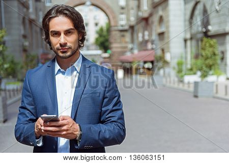 Portrait of attractive young businessman standing on street. He is holding a mobile phone and messaging. Man is looking at camera with confidence. Copy space in right side