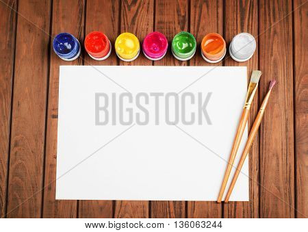 Paints and brushes on a white blank sheet of paper on wooden background