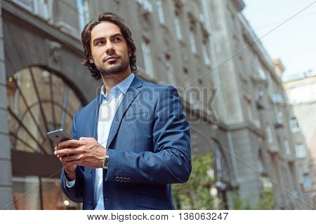 Young man is using a mobile phone. He is standing outdoors and looking aside pensively