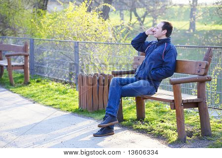 Man Sitting On A Park Bench Talking On Cell Phone
