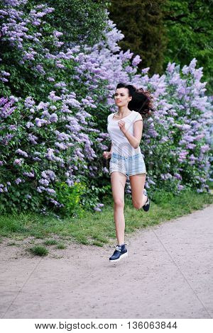 young beautiful woman jogging in spring park
