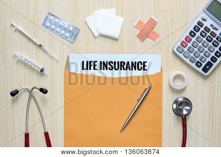 Top view of Life Insurance with letter envelope stethoscope hypodermic syringe plaster gauze medicine tape and calculator.
