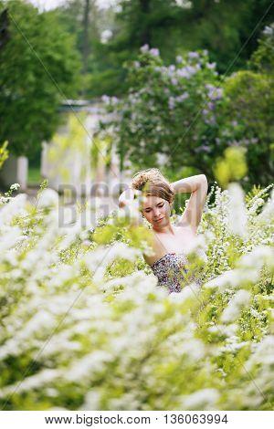 beautiful girl in a big spirea bush