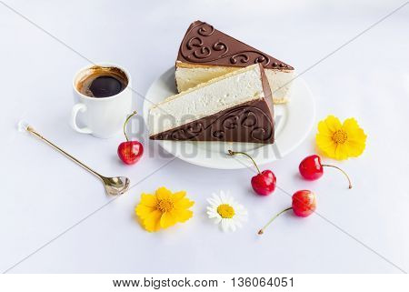 Milk souffle cakes with chocolate glaze on a plate, coffee in a cup, spoon, ripe cherries and flowers on a white tablecloth