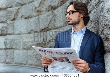 Confident young businessman is waiting for someone. He is standing and leaning on the wall. Worker is holding a newspaper and looking aside with anticipation