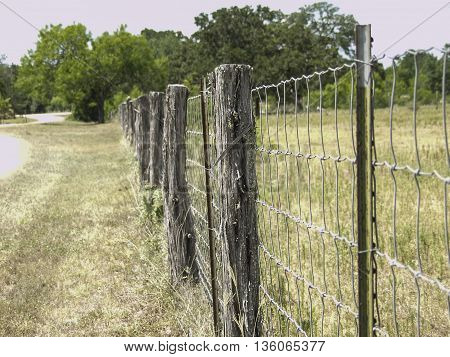 A wooden picket fence with a wire mess.