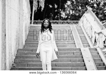 Young African American Girl, Dressed In White, Walking On Stairs Of City