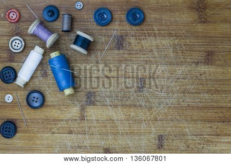 Sewing accessories. Spools, buttons, needles on wooden background. Set for handmade. Top view