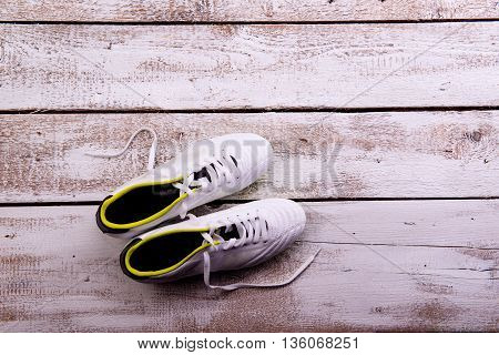 Soccer Cleats Against Wooden Background. Studio Shot. Copy Space