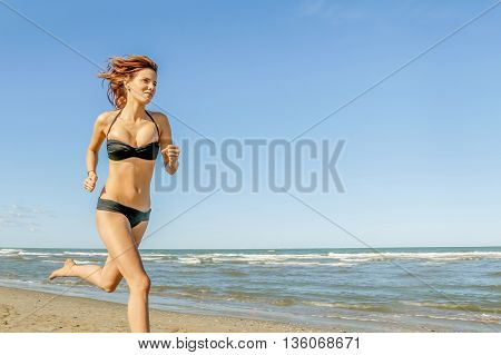 young woman in bikini in beautiful shape jogging on the beach on a sunny day - concept of fitness and healthy lifestyle