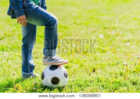 Close up of boy putting leg on the ball. He is standing on grass. Copy space in right side
