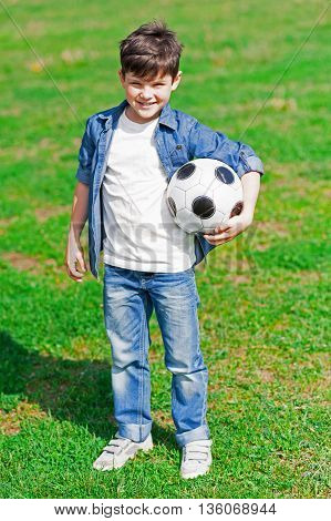 Portrait of cute male child playing football. He is standing on grass and holding a ball. The kid is looking forward and smiling happily