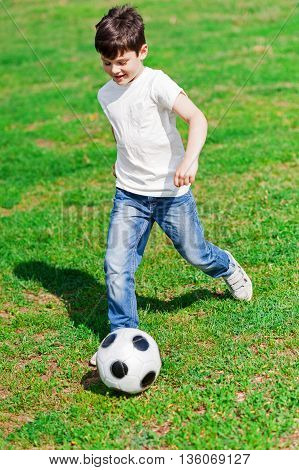 Cheerful boy is running and kicking the ball by his foot. He is laughing