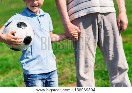 Pretty small boy is holding a ball and smiling. He is holding hand of grandfather. They are standing on grass in a park