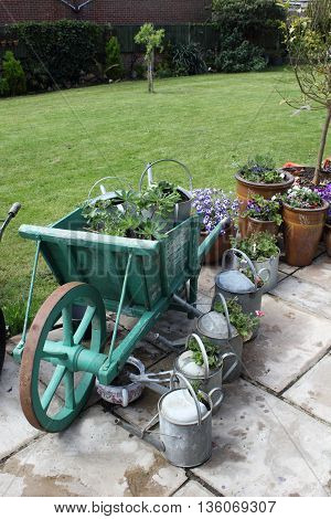 An english garden with a vintage wheel barrow and watering cans being used as planters for flowers