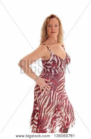 A portrait image of a blond woman in a summer dress standing in profile with one hand on hip isolated for white background.