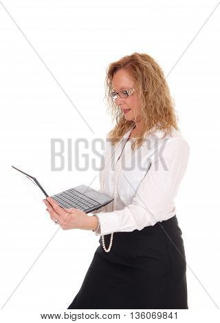 A business woman standing in a black skirt and white blouse holding her laptop and working with isolated for white background.