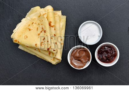 french pancake with pots of sugar jam and chocolate on dark background