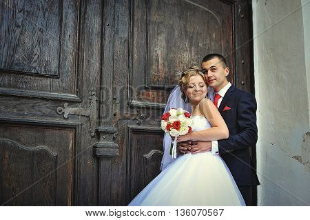 Wedding Couple On The Background Of Old Wooden Door