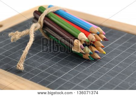 package of colored pencils on a slate on white background