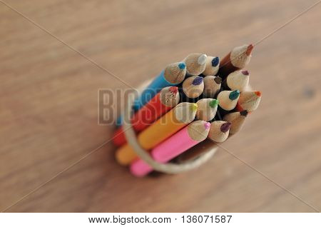 package of colored pencils on wooden background