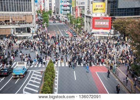 Tokyo Japan - November 21 2015: Unidentified pedestrians walk at Shibuya Crossing one of the busiest crosswalks in the world in Tokyo Japan.