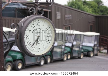 10TH JUNE 2016, OKEHAMPTON, ENGLAND: A clock on the first tee with golf buggies in the background on a golf course at okehampton,england, 10th june 2016