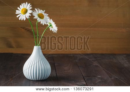 Bouquet daisies in a white vase on wooden table