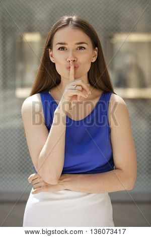 Young beautiful brunette woman has put forefinger to lips as sign of silence, against shop window