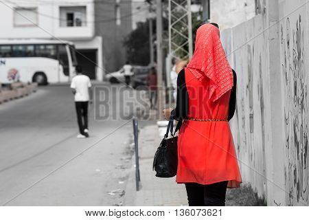 Modest fashionable young eastern Arabic woman walking down gray street in bright red dress
