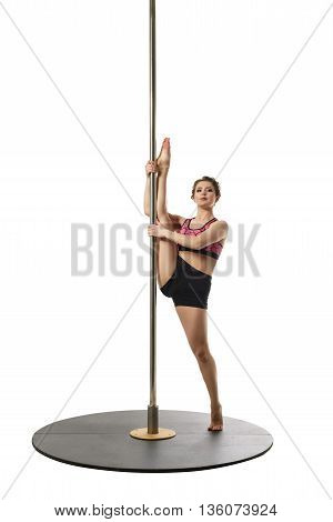 Flexible girl trains on pylon, isolated over white backdrop
