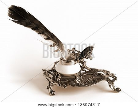 Sepia toned Photo shows Ornate antique brass inkwell with feather