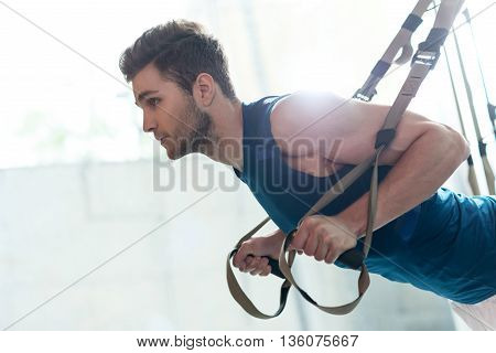 Attractive fit sportsman training in gym. He is leaning on trx strap and doing push-ups. Man is looking forward with confidence