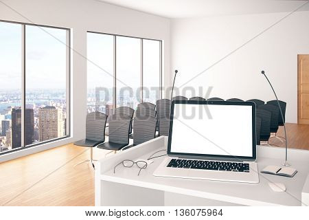 Conference hall interior with blank white laptop on stand with microphones glasses and windows with city view. Mock up 3D Rendering